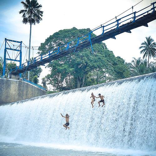 People enjoying in water splashing against sky