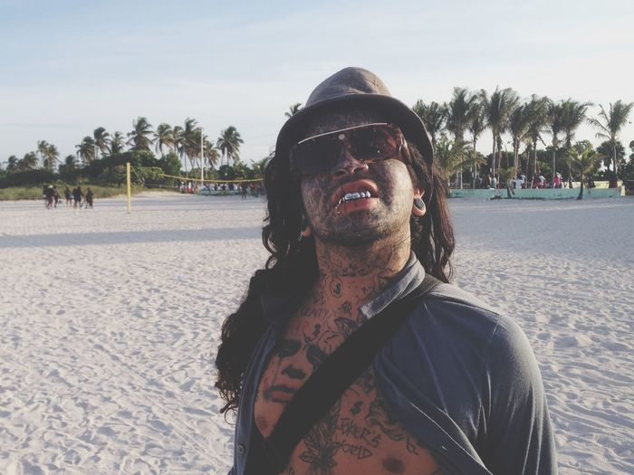 Funky man with facial tattoo on beach