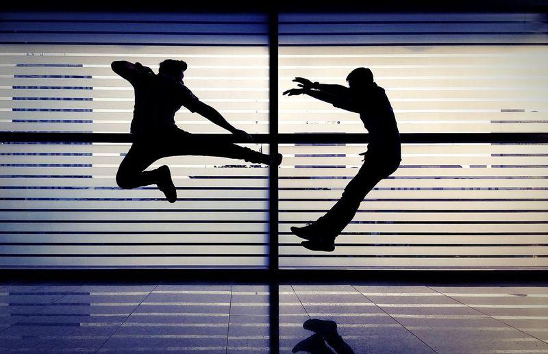 Silhouette man kicking enemy against window