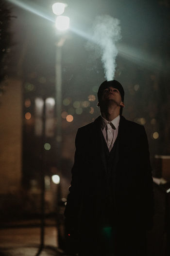 Young man smoking at night