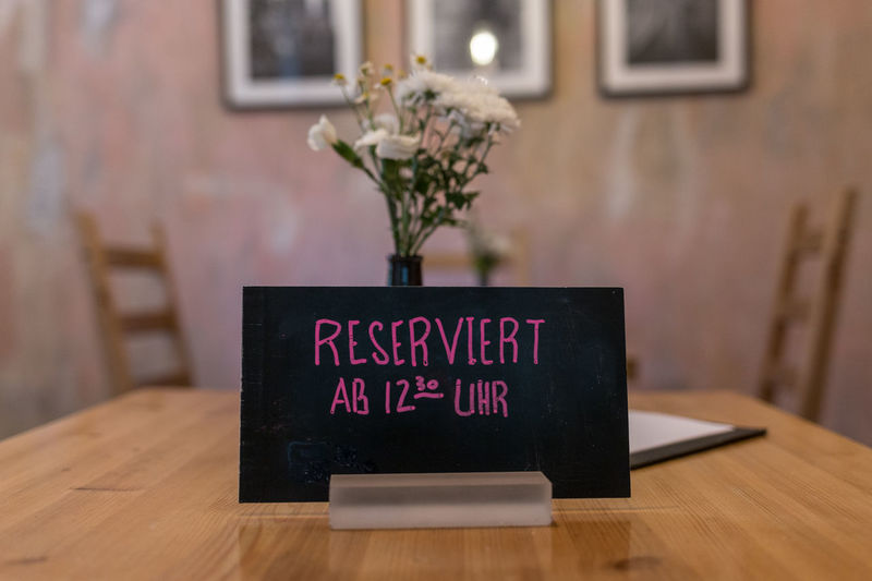 Communication Focus On Foreground Indoors  No People Picture Frame Reservation Restaurant Seat Table Tables Text Vase Western Script Wood - Material