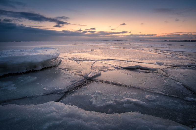 Scenic winter landscape with frosty sea and sunset at evening in Helsinki, Finland Coastline Evening Light Finland Frost Helsinki Ice Nature Tranquility Travel Winter Adventure Atmospheric Mood Beauty In Nature Cold Temperature Dawn Dusk Icy Landscape Ocean Sea Seascape Sky Snow Sunrise Sunset