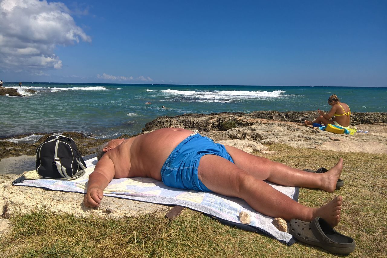 MIDSECTION OF MAN RELAXING ON BEACH AGAINST SKY