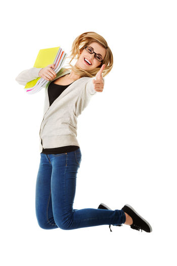 Smiling young woman holding spiral notebooks while jumping against white background