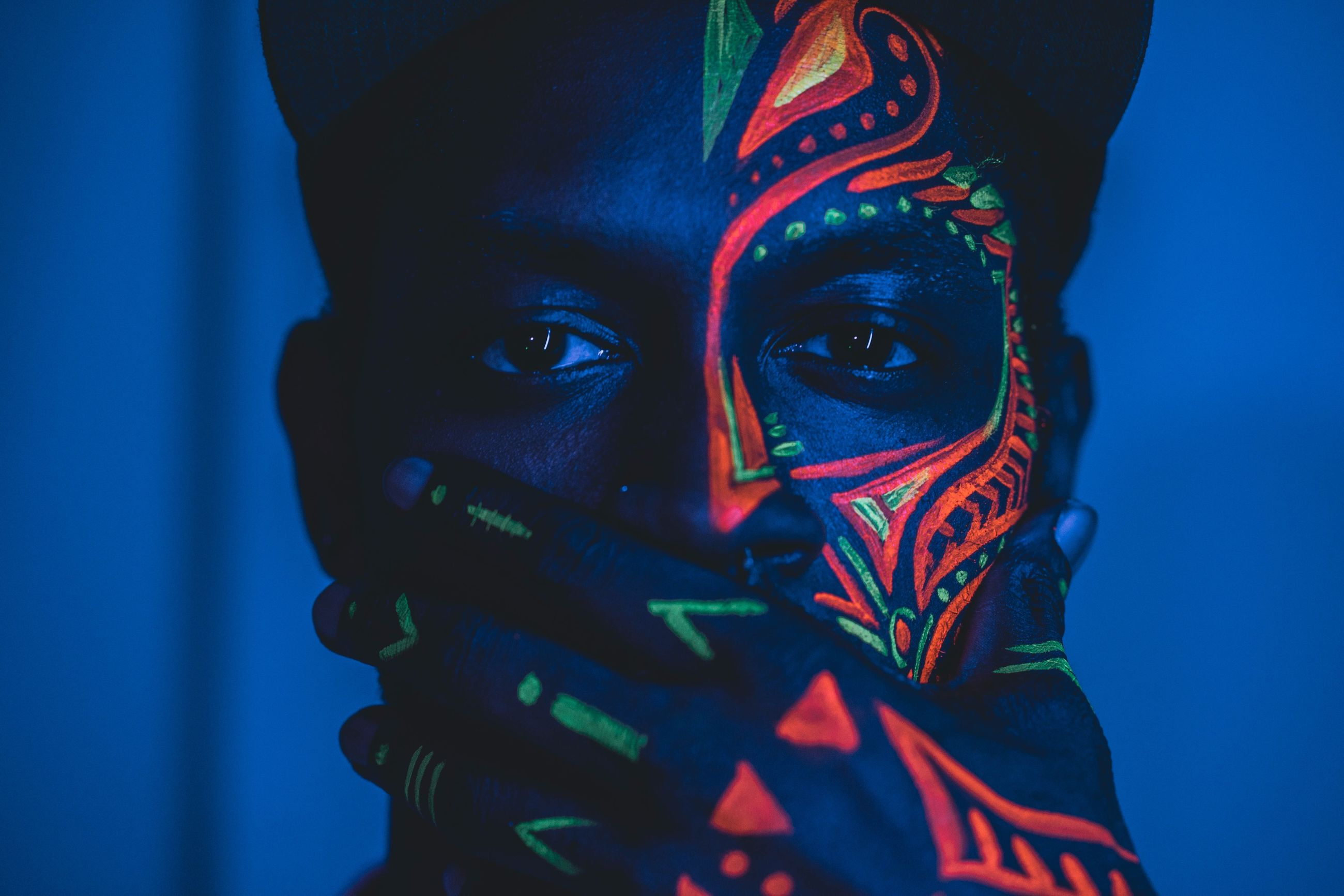 one person, portrait, headshot, body part, front view, human body part, young adult, indoors, looking at camera, multi colored, close-up, real people, human face, paint, lifestyles, young women, leisure activity, adult, light - natural phenomenon, obscured face, blue background, scarf, teenager