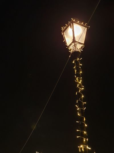 Low angle view of illuminated light bulb against sky at night