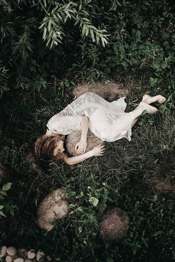 Young alone woman lying on the grass in the forest and hugging a stone. dark mood.