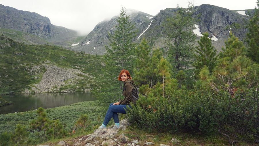 Full length of young woman against plants and mountains