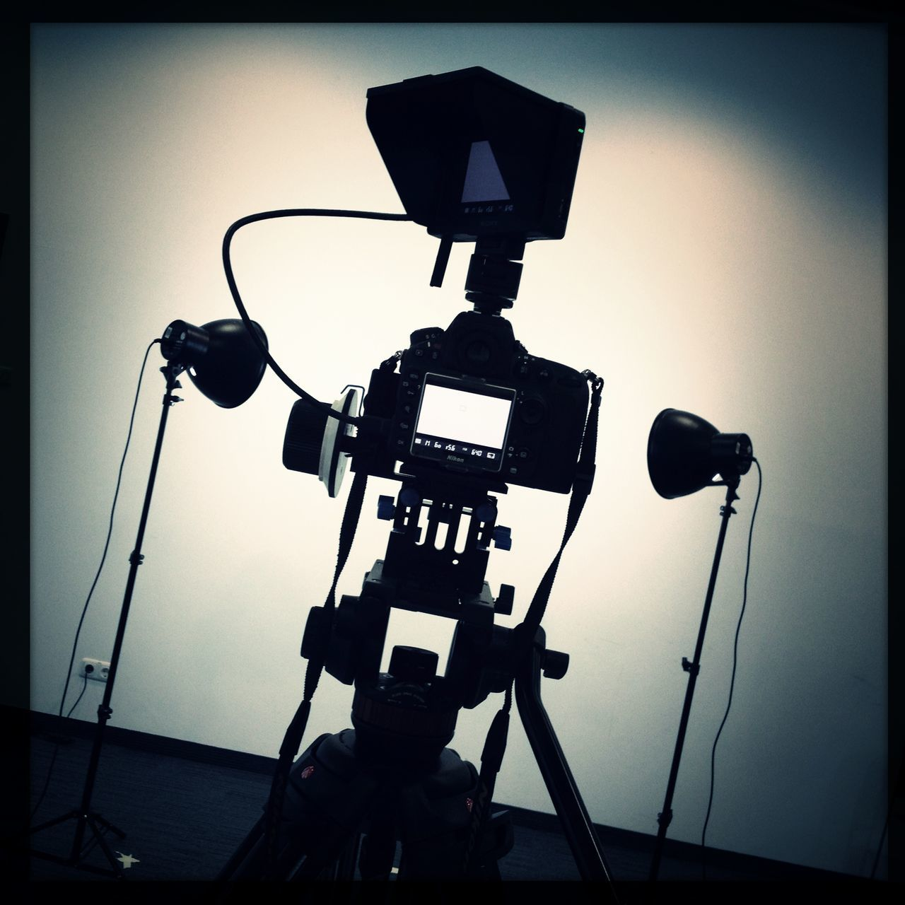 tripod, film studio, lighting equipment, silhouette, photography themes, technology, illuminated, camera - photographic equipment, cable, behind the scenes, film industry, photographing, no people, indoors, sky, television studio, day