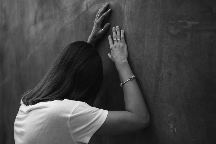Side view of sad woman standing by wall