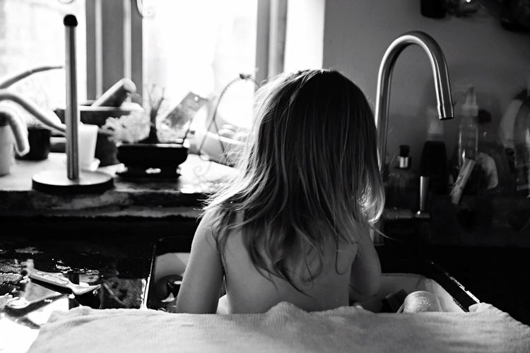 Rear view of girl sitting in kitchen sink