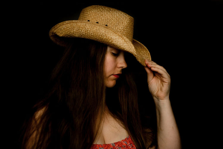 Portrait of woman wearing hat against black background