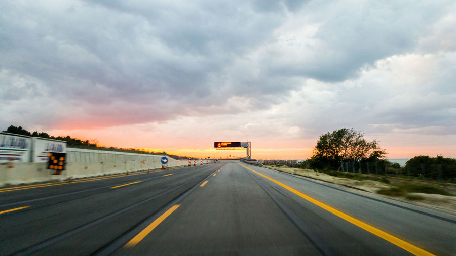Empty Road Against Cloudy Sky During Sunset