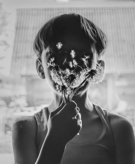 Close-up portrait of a boy blowing dandelion seeds