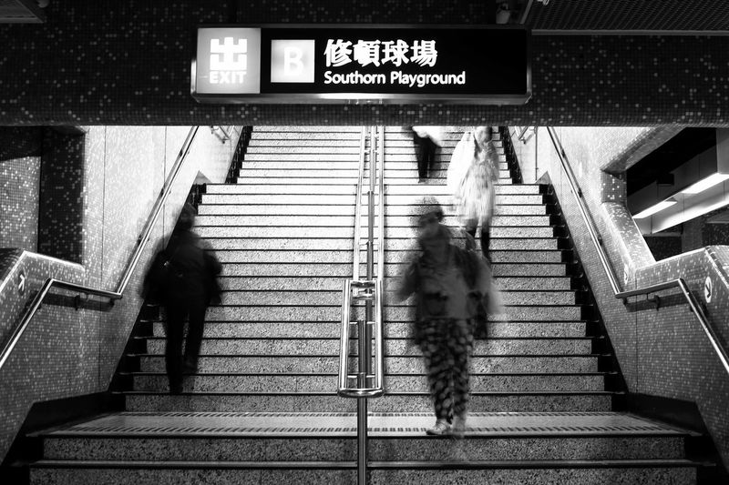 Blurred motion of people walking on steps at subway station