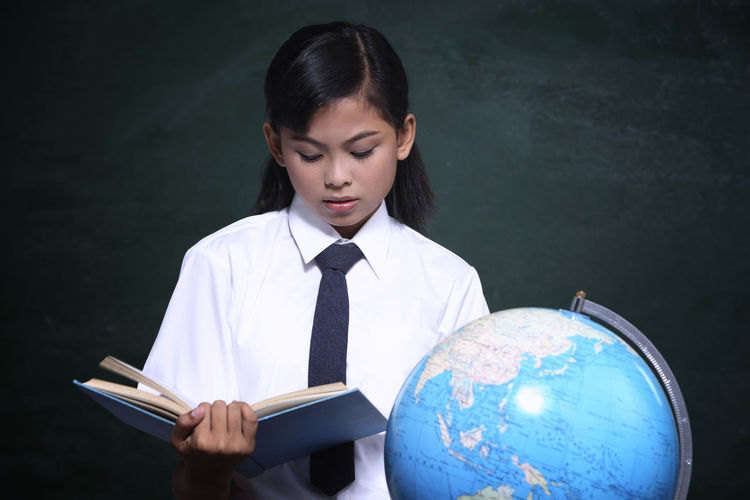 Schoolgirl reading book by globe against blackboard