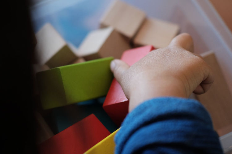 Cropped Image Of Kid Playing With Toy Blocks At Home