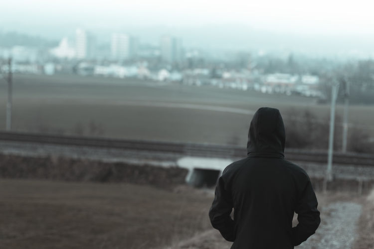 back of young man with hoodie watching to the city Outskirts Town Loneliness Lonely Emigration Hoodie Back Landscape Nature City Watching View Hipster Concept Nature Standing Excluded Reject Emitted Rejection
