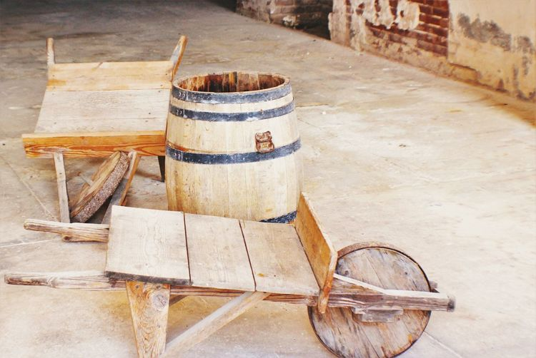 Wine cask and wooden cart outside winery