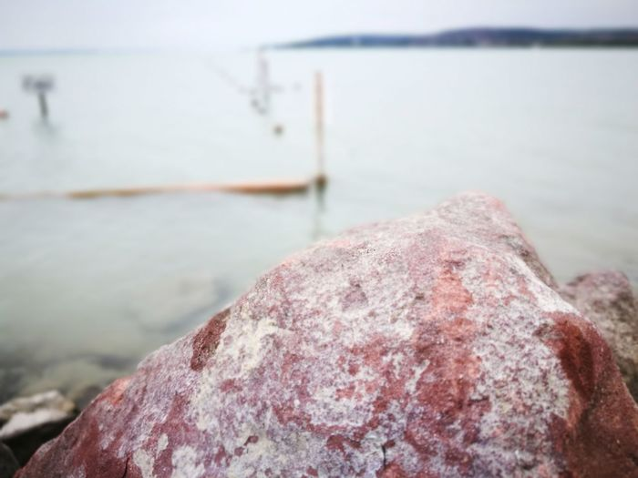 Close-up of rock by river against sky