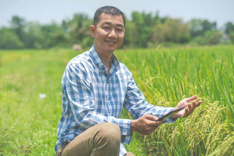 Portrait of smiling farmer with digital tablet holding crops on field