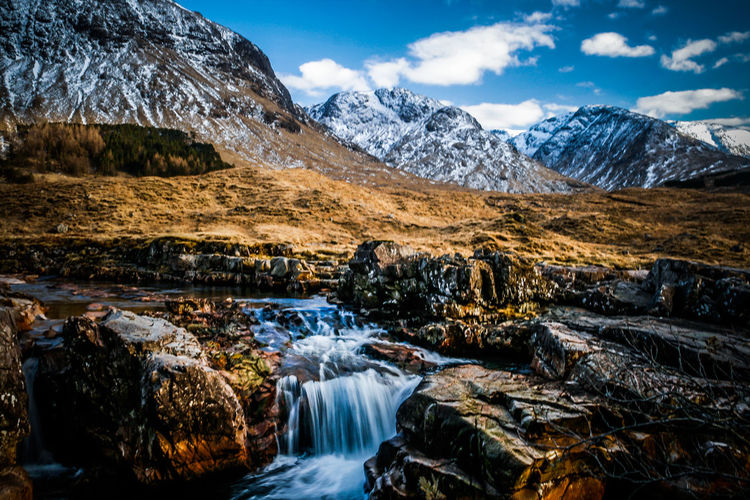 Scenic view of waterfall against mountains during winter
