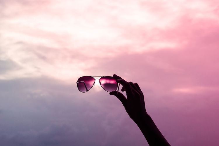 Silhouette hand holding sunglasses against sky during sunset