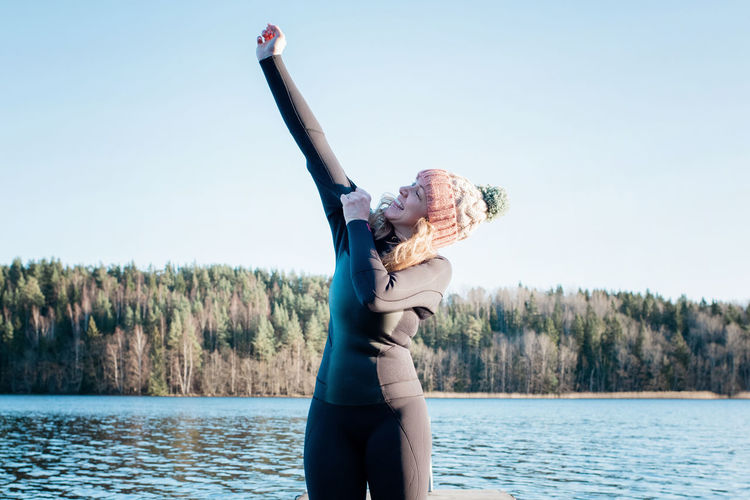 Woman with arms raised in lake against sky