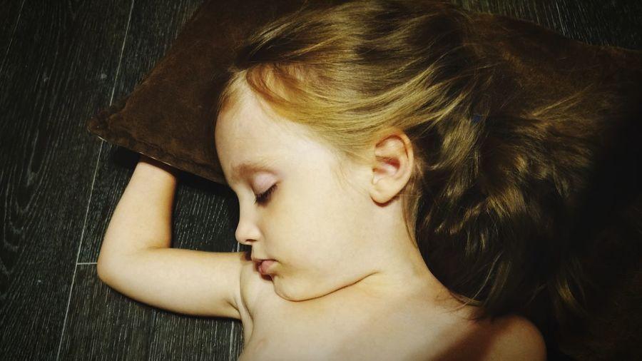 Close-up of shirtless girl sleeping on hardwood floor