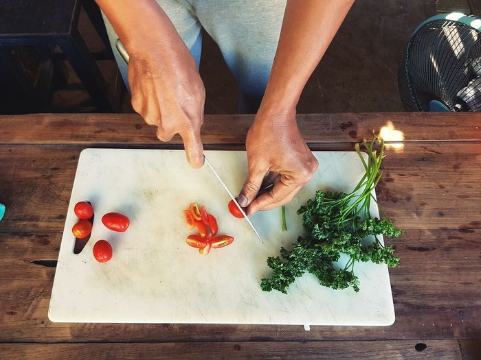 Midsection Of Woman Chopping Tomatoes On Cutting Board At Table