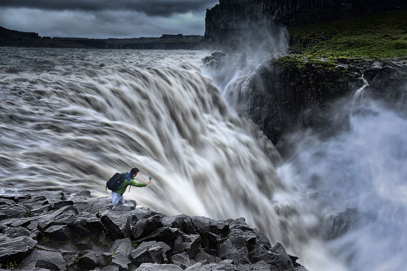 View of man photographing dettifoss waterfall
