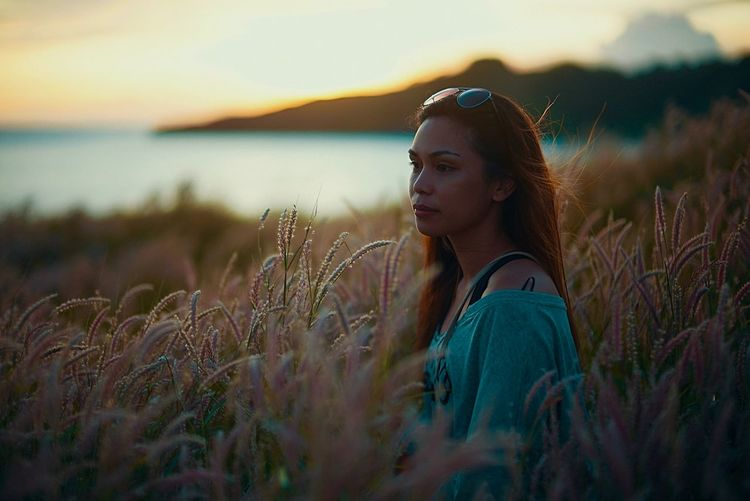 Young woman standing on grass against sky during sunset