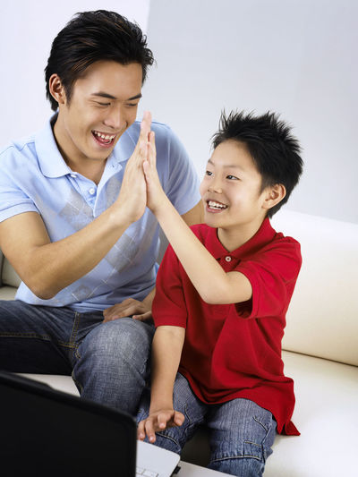 Happy Father Giving High-Five To Son While Sitting On Sofa