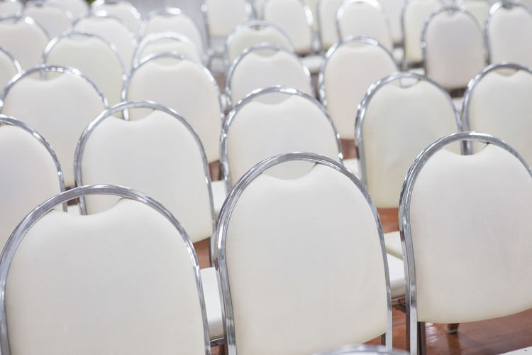 White chairs arranged in a seminar room In A Row Seat Chair Empty No People Order Large Group Of Objects Side By Side Absence Repetition White Color Arrangement Indoors  Group Of Objects Arranged Seminar Seminar Room Close-up Auditorium Focus On Foreground Group Backgrounds Business Blank Silver Colored