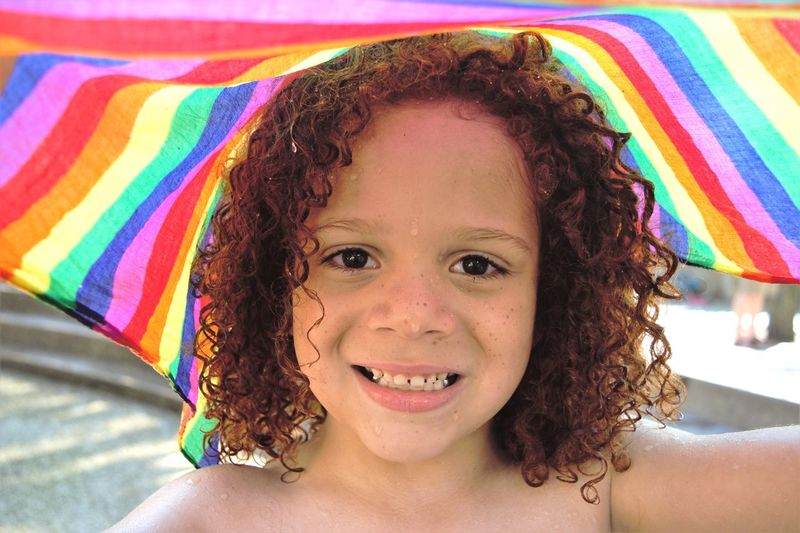Portrait of smiling boy with wet curly hair and colorful textile