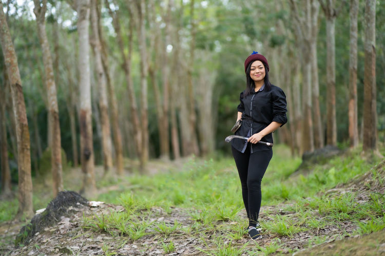 Full length portrait of woman with equipment in forest