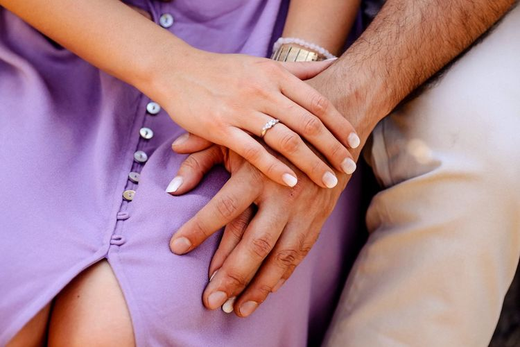Midsection of couple holding hands during engagement ceremony