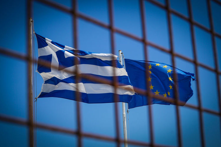 Flags of Greece and the EU European Union Europe behind a fence in the harbour of Kos island, Greece, in June 2017. Border Day Eu Europe European Union Europäische Union Fence Flag Flaggen Flags Greece Greek Grenze No People Outdoors Rettungsschirm Wind