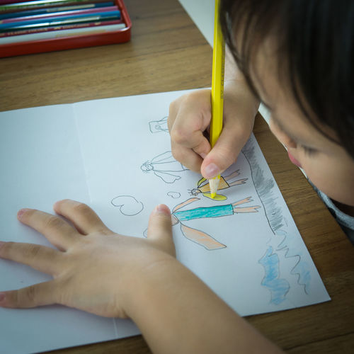 High angle view of girl drawing on paper at home