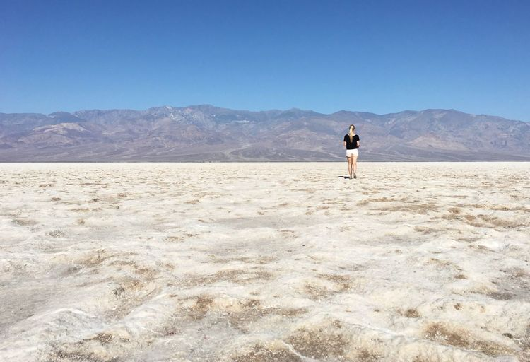 Rear view of woman standing on salt flat at death valley