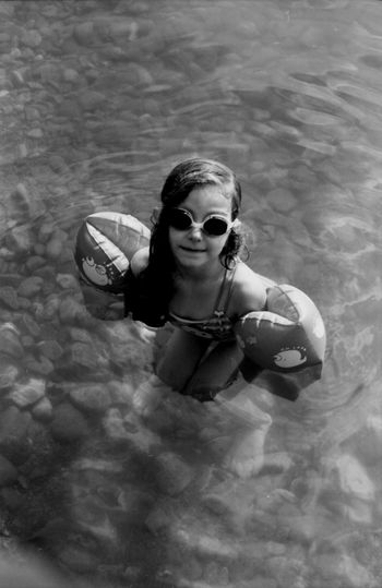 High Angle View Of Girl Wearing Sunglasses Standing In Sea
