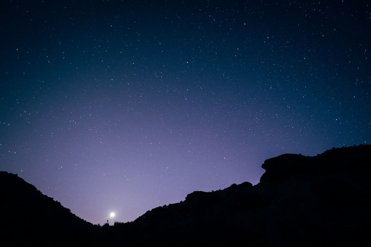 Low angle view of silhouette mountain against star field at night