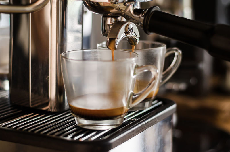 Close-up of coffee maker pouring coffee in cup