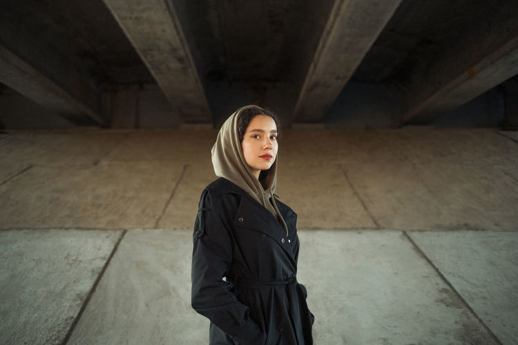 Portrait of beautiful young woman standing in concrete