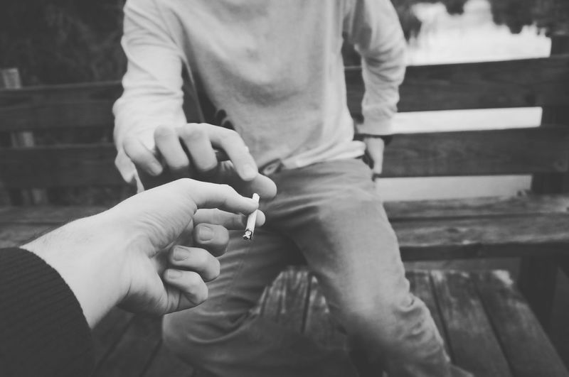 Male friends sharing cigarette