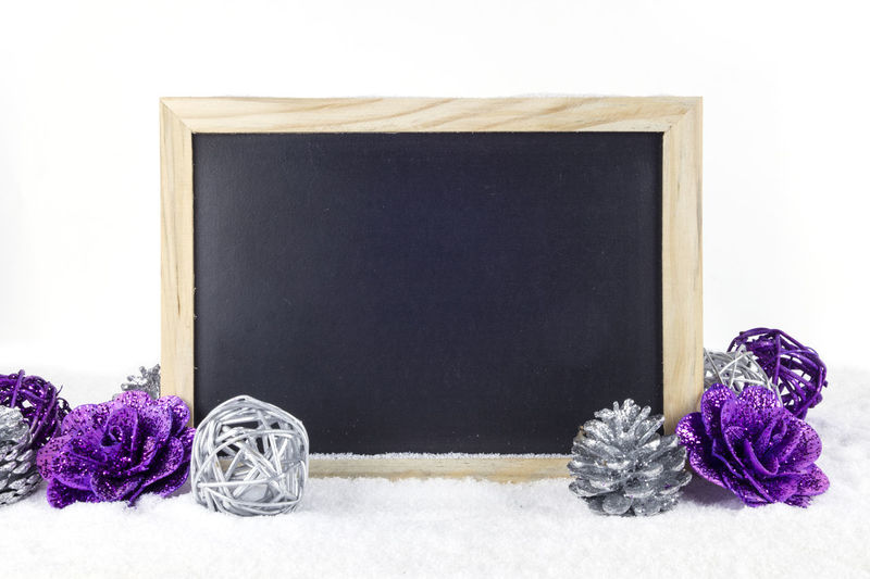 Close-up of blackboard with christmas decorations on snow