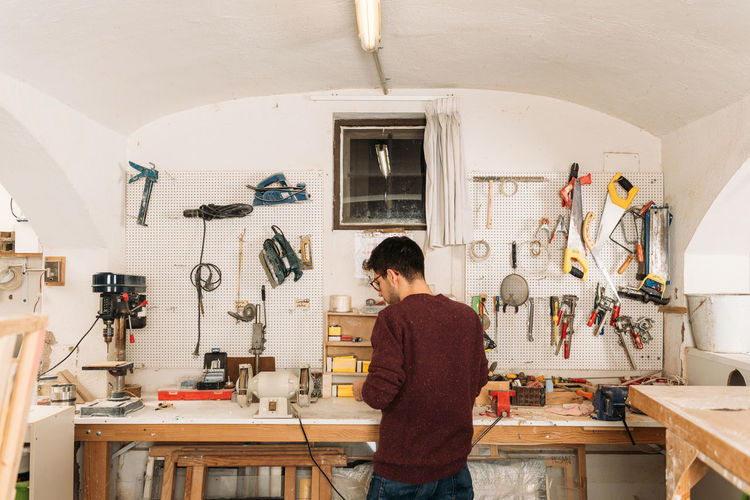 Rear view of man working on table