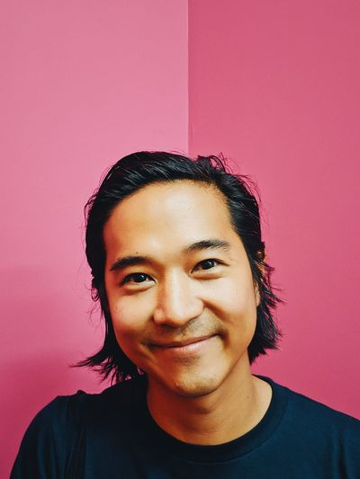 Portrait of smiling young man against pink wall