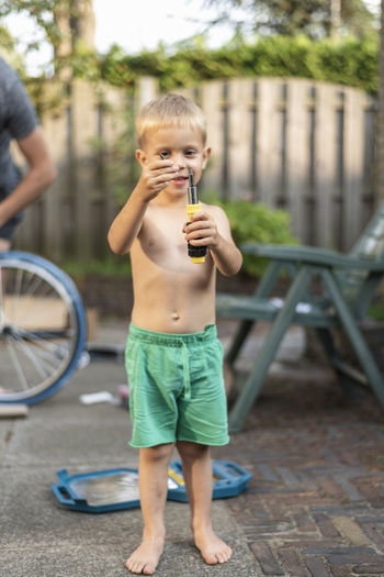 Full length of shirtless boy holding tool while standing outdoors