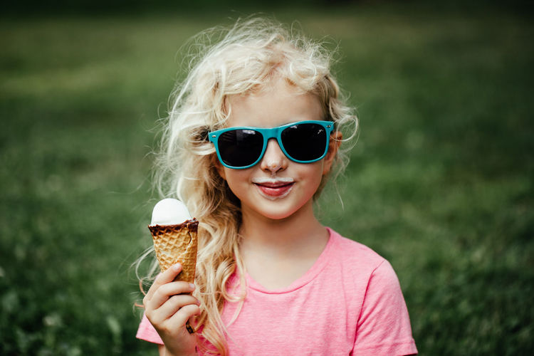 Cute funny girl in sunglasses with dirty nose and moustaches eating ice cream from waffle cone